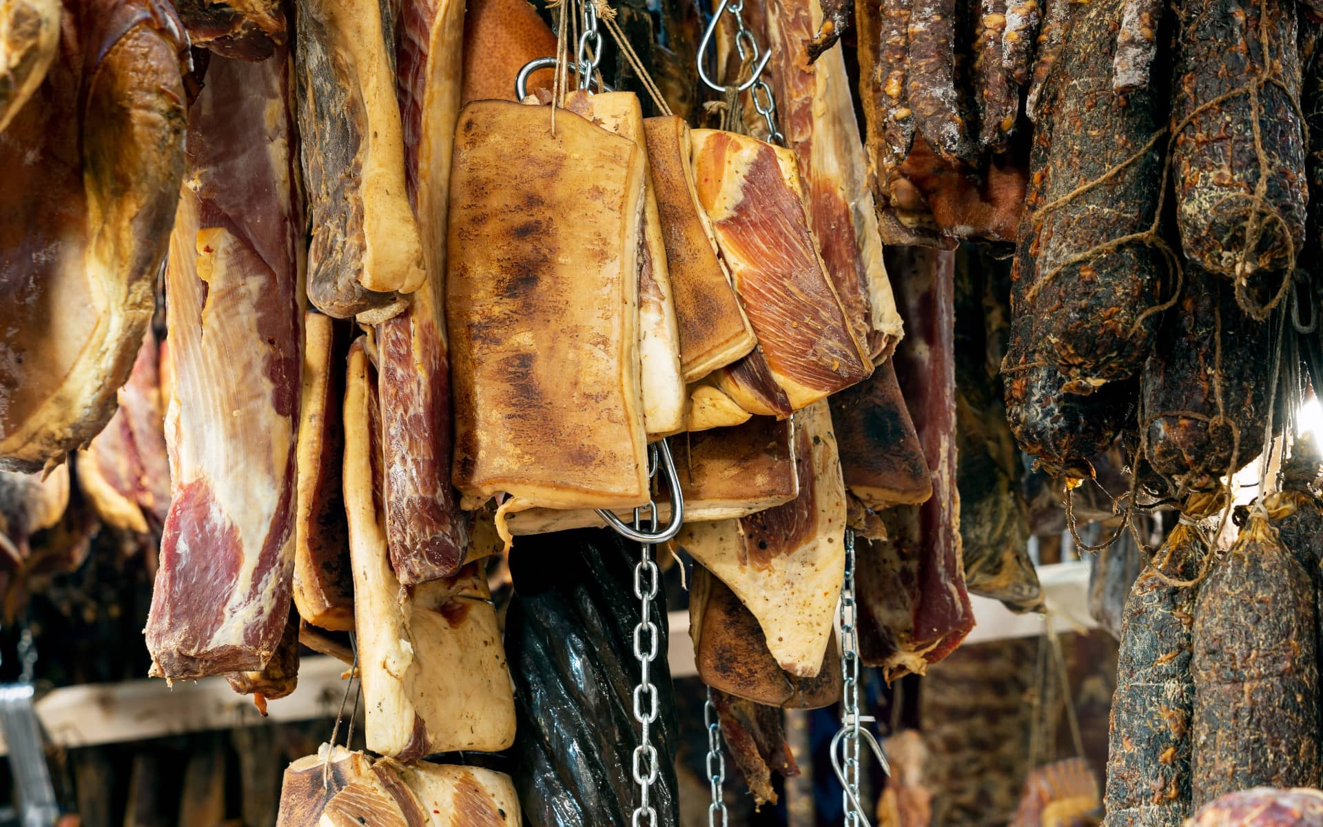 Smoked meats hanging from hooks.